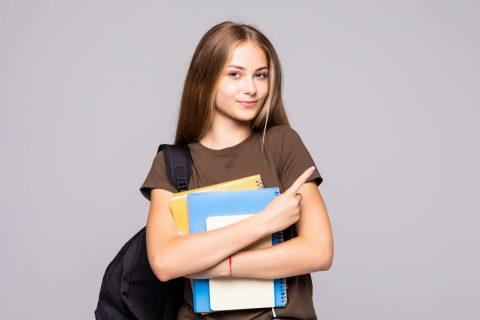 Portrait of cute young brunette student holding exercise books isolated on white background
